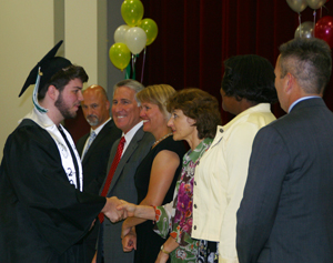2014 graduate shaking hands with board