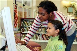 Volunteer helping student on computer