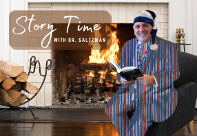 Dr. Saltzman sitting in front of a fire reading a book wearing funny pajamas and a night cap.
