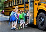 Elementary students getting on school bus