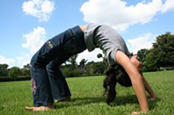 Girl doing backbend on the grass
