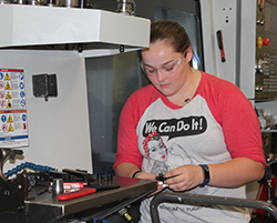 Female high school student working with large industrial machine