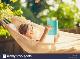 photo of teenager reading a book while relaxing outside in a hammock